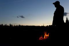 Силуэт охотника с лагерным костером Стоковые Фото