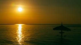 Силуэт парасоля на заходе солнца красивого моря тропическом Стоковые Фото