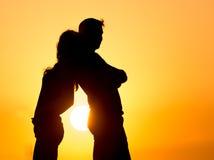 Силуэт парня и девушки на заходе солнца Стоковая Фотография RF