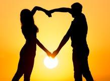 Силуэт парня и девушки на заходе солнца Стоковая Фотография
