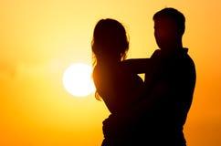 Силуэт парня и девушки на заходе солнца Стоковое Фото
