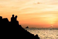 Силуэт пары наблюдая красочный заход солнца Стоковое Изображение RF
