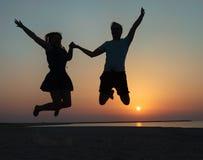 Силуэт пары - человек и женщина скача на пляж Стоковое Изображение RF