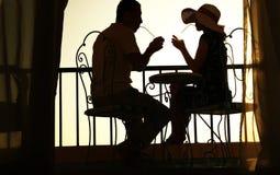 Силуэт пар в влюбленности выпивает питье Стоковые Изображения