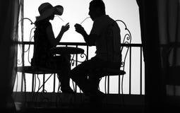 Силуэт пар в влюбленности выпивает питье Стоковое фото RF