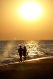 Силуэт пар влюбленности идя на пляж Стоковое фото RF