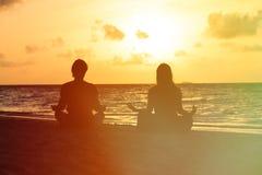 Силуэт пар делая йогу на заходе солнца Стоковая Фотография RF