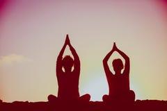 Силуэт пар делая йогу на заходе солнца Стоковое Изображение
