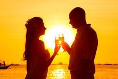 Силуэт пар наслаждаясь стеклом шампанского на тропическом bea Стоковое Изображение