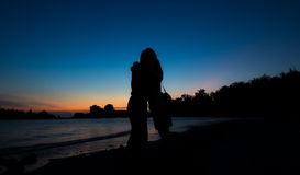 Силуэт пар обнимает на пляже после захода солнца Стоковая Фотография RF