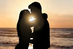 Силуэт пар целуя на пляже во время захода солнца Стоковое Изображение RF