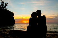 Силуэт пар setaed перед заходом солнца Стоковые Изображения