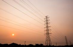 Башни передачи силы с заходом солнца Стоковое Фото