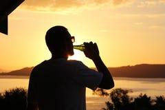 Силуэт пива человека выпивая на заходе солнца Стоковое Изображение RF