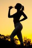 Силуэт питьевой воды девушки после внешней разминки Стоковая Фотография RF
