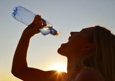 Силуэт питьевой воды женщины от бутылки Стоковое Фото