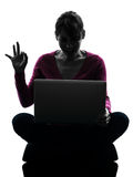 Силуэт портативного компьютера жеста о'кей женщины вычисляя Стоковая Фотография RF