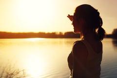 Силуэт природы захода солнца молодой женщины наблюдая Стоковые Фото