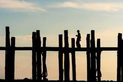 Силуэт прогулки женщины на мосте U-Bein, ориентир ориентир Мандалая, Стоковые Изображения RF
