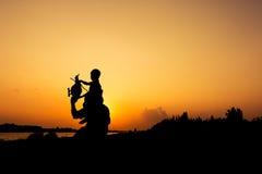 Силуэт плана папы и сына строгает заход солнца стоковые фото