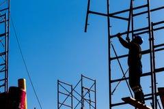 Силуэт рабочий-строителя против неба на острословии лесов Стоковые Изображения