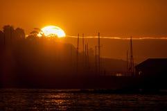 Силуэт рангоутов кораблей против захода солнца над гаванью Стоковое фото RF