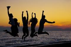 Силуэт друзей скача на пляж во время времени захода солнца Стоковое фото RF