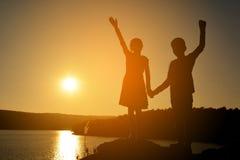 Силуэт руки мальчика и девушки открытой на утесе Стоковые Изображения RF