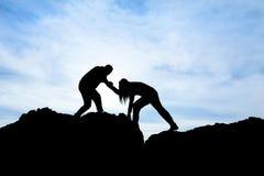 Силуэт руки помощи между альпинистом 2 Стоковое Изображение
