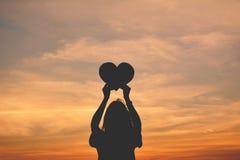 Силуэт рук женщин держа форму сердца Стоковые Изображения RF