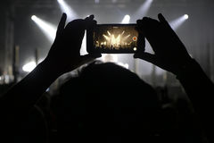 Силуэт рук записывая видео на концерте музыки Стоковые Изображения RF