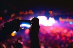Силуэт рук используя телефон камеры для того чтобы принять изображения и видео на концерт музыки, фестиваль Мягкое влияние на фот Стоковое Фото