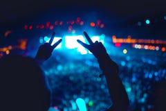 Силуэт рук показывая влюбленность для художников на концерте, фестивале Предпосылка светов agains жестов рукой Стоковое Изображение