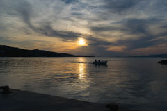 Силуэт рыбацкой лодки возвращающ к порту против драматического неба Стоковые Изображения