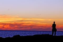 Силуэт рыбной ловли парня Стоковые Изображения RF