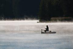 Силуэт рыболова в тумане раннего утра Стоковое фото RF