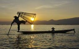 Силуэт рыболова на заходе солнца. Стоковое Изображение RF