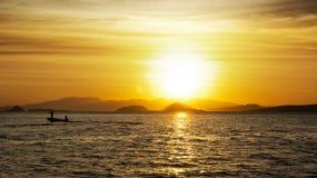 Силуэт 2 рыболовов на малой рыбацкой лодке с забортным двигателем на океане на наступлении ночи с оранжевым заходом солнца Стоковое Изображение RF