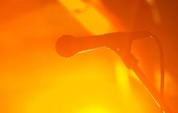 Силуэт связанного проволокой микрофона против оранжевой предпосылки двуколки концерта Стоковая Фотография RF