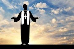 Силуэт священника моля против неба вечера Стоковые Изображения RF