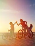 Силуэт семьи велосипедиста на заходе солнца Стоковые Фотографии RF