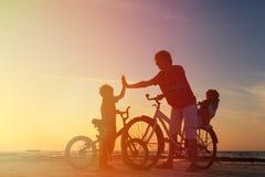 Силуэт семьи велосипедиста, отец с 2 детьми дальше Стоковое фото RF