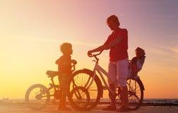 Силуэт семьи велосипедиста, отец с 2 детьми на велосипедах на заходе солнца Стоковое Изображение RF