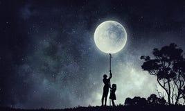 Силуэт семьи на предпосылке ночи Мультимедиа Стоковое Фото