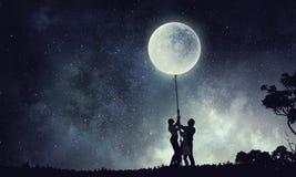 Силуэт семьи на предпосылке ночи Стоковое фото RF
