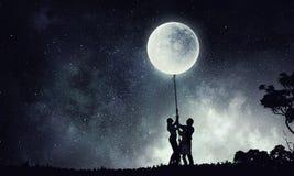 Силуэт семьи на предпосылке ночи Стоковая Фотография