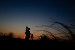 Силуэт семьи с ребенком в поле Стоковая Фотография RF
