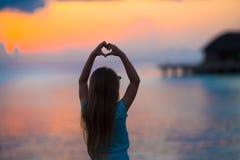 Силуэт сердца сделанный рукой детей на заходе солнца Стоковое Изображение RF
