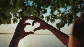 Силуэт сердца сделанный рукой маленькой девочки на заходе солнца романтичная тема акции видеоматериалы
