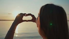 Силуэт сердца сделанный рукой маленькой девочки на заходе солнца романтичная тема сток-видео